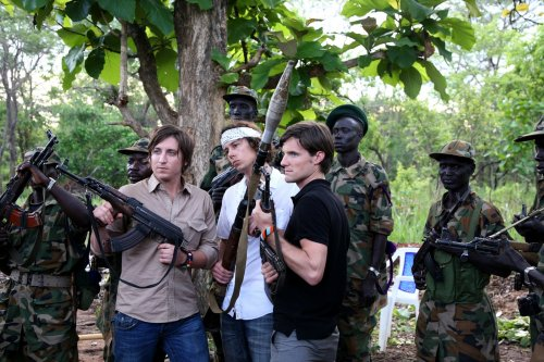 Invisible Children Founders pose with weapons from the SPLA